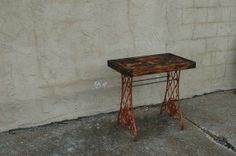 Steampunk inspired side table built from antique Singer sewing machine table legs, machine thread and aspen.    Work by Architectural Elements, St Louis, MO