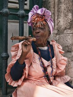 Bata Cubana Antigua: An older Cuban woman in colourful traditional costume poses playfully with her cigar outside the Plaza de Armas. Cuban Women, Havana Nights Party, Mode Boho, African Diaspora, Women Smoking, People Of The World, Black Is Beautiful, Belle Photo, Black Girl Magic
