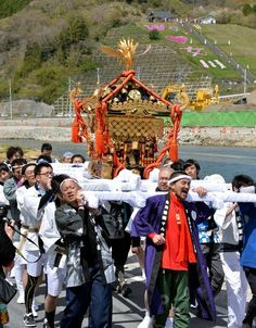 Volunteers from around Japan, along with local residents, shoulder a portable shrine in Onagawa, Miyagi Prefecture, on May 3. (Kengo Hiyoshi)