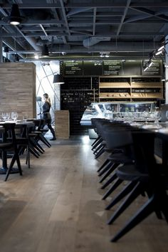 KNRDY Restaurant by Budapest based Suto Interior Architects, with exposed ceiling, beams and ducts, painted black