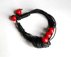 http://www.designspinka.pl/bransoletka-4/ Bransoletka z wiśniowymi, drewnianymi koralikami w rozmiarze około 12mm, na czarnym, woskowanym sznurku.