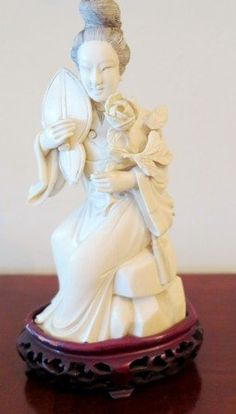 Quan Yin figure holding a rose and a lute. The whole resting on a carved teakwood base.