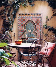 Gillian Anderson's courtyard patio. >> Wonder how easy to create a similar tile mosaic over/around a simple (boring) wall fountain?