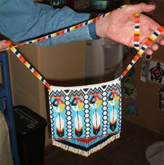 Handmade beaded purse in Native American style, turquoise and feathers motif with sunset stripes on shoulder strap