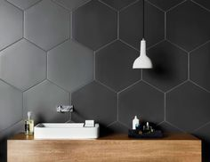 Bathroom Tile Ideas - Grey Hexagon Tiles // Large hexagonal charcoal tiles on the walls of this bathroom create a unique, modern look that compliments the wood countertop and contrasts the white sink and light fixture. Hexagon Tile Bathroom, Hexagon Tiles, Bathroom Flooring, White Bathroom, Modern Bathroom, Hex Tile, Honeycomb Tile, White Shower, Tiling