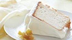 """Remember Mom's heavenly angel food cake? Ours has the same ethereal texture but with a bright burst of lemon flavor, thanks to fresh juice and zest. Fluffy citrus cream frosting and pretty candied lemon """"daffodils"""" make it even more memorable."""