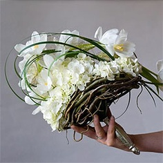 A fashionable bridal bouquet with handmade nesting around the base and a waterfall of lily grass flowing over the bouquet.