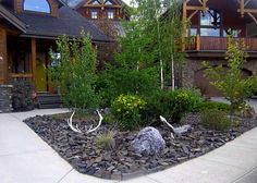 Black Rock Landscaping Ideas For Front Yard With Some Small Green Plants And Brown Wood Wall Black Roof  In Sweet Exterior