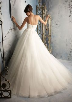 I am selling my beautiful size 6 Mori Lee, white, tulle ball gown bridal gown. This gown has a fitted ASYMMETRICAL, sweetheart top that transitions in to a natural waist line and a full skirt. This dress has had some minor alterations but has been REASSEMBLED, by a seamstress back to its original fit. The SIDE SEAMS were let out so that it would fit closer to a size 8 and the belt that came with the dress was reconstructed to a more simpler design. The hem has not been altered in any way…