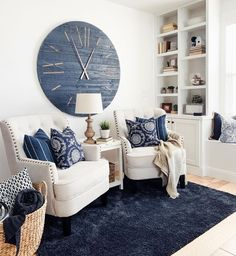 Large navy blue clock on wall behind two matching cream colored chairs. Navy rug with paisley and navy ticking pillows. Blanket basket and built-in shelves in corner. Blue And Cream Living Room, Blue Living Room Decor, New Living Room, Living Room Chairs, Living Room Designs, White Decor, Navy Home Decor, Living Room Inspiration, Decoration
