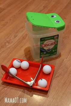 Fine motor practice for toddlers and preschoolers with tongs, ping pong balls, and an empty detergent bottle that looks like a googly-eyed crocodile! #finemotor #mamaot