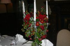Fresh flower silver candelabra with burgundy roses , berries  and trailing foliage