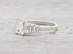 Art Deco ring made in platinum and centered with a 1.26 carat GIA certified emerald cut diamond with I color and VS2 clarity. Accented with three baguette cut diamonds on each shoulder.Signed Tiffany & Co. Circa 1935 A truly remarkable ring made by Tiffany & Co during the height of the Art Deco era. This piece features a step setting and an elegantly low profile.Learn more about emerald cuts Diamond and gold mining has caused devastation in areas such as Africa, wreaking havoc on delicate…