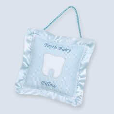 The Le Petite Tooth Pillow has a small pocket on the front is a perfect place for your child to place their treasured baby teeth while they wait for the tooth fairy to arrive. It has a handy chord for hanging over the door knob or head board of wherever your child decides is the best place to catch the tooth fairy's attention