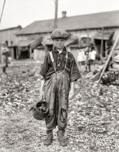 """February 1912. """"Henry, 10-year-old oyster shucker who does five pots of oysters a day. Works before school, after school, and Saturdays. Been working three years. Maggioni Canning Co., Port Royal, South Carolina."""" Glass negative by Lewis Wickes Hine for the National Child Labor Committee."""
