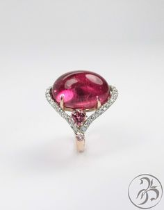 Rubelite Tourmaline cabachon cocktail ring with pink tourmaline, diamonds and 2 small pink sapphires. Set in both rose and white gold, and available from Redford Jewelers in Salt Lake City.