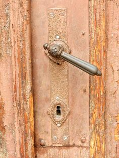 An old, XIX century (or even older) door handle on a saumon pink wooden door with cracked paint in downtown area of Sibiu, Transylvania, Romania, Europe.