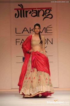 Nude lehanga with floral design. Pink dupatta. Pink flowers and green leaves. Outfit by Gaurang Shah at the Lakme Fashion Week, India.