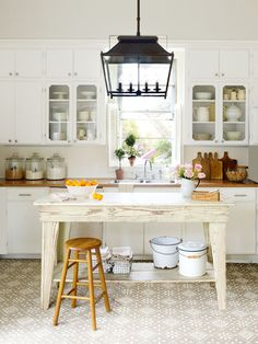 This farmhouse kitchen has butcher block countertops, indoor/outdoor rug to cover the old floors, and beadboard wallpaper backsplash.