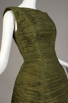 This dress is by Irish designer Sybil Connolly known for her pleated dresses made of Irish linen. Detail of pleated green cocktail dress, Sybil Connolly, 1960s, KSUM 1989.10.2.