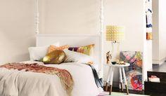 couleur peinture chambre - nuance de blanc, panneau abstrait multicolore et coussins à motifs variés