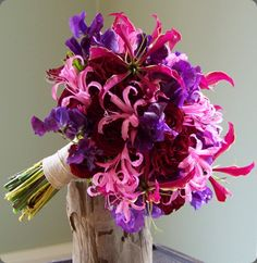 Purple orchids, pink nerine,  gloriosa lily and red roses by floral verde