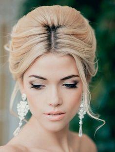 Braut mit eleganter Hochsteckfrisur und wunderschönem Make-up mit Nude Lippen.