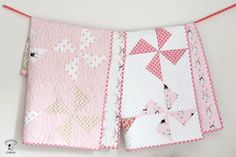 Are you searching for a DIY baby gift? Try sewing this Pink Pinwheel Baby Quilt for your next baby shower! This pinwheel quilt tutorial uses fat quarters and the half square triangle quilting technique to create a pretty pinwheel effect.