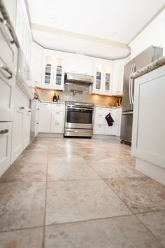 Beautiful tan tile floors to match the all white cabinets. www.choosechi.com