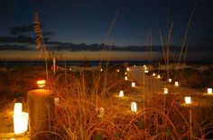 Luminaria candles and sea oats at beach wedding barbecue in Indian Shores, Florida