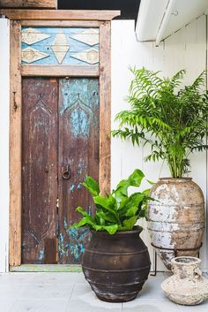 Outdoor space with a rustic door and vintage pots Architectural Landscape Design