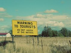 sign. warning to tourists. do not laugh at the natives
