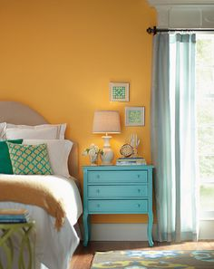 Decorating Ideas: Bold paint choices aren't restricted to walls, why not jazz up an old furniture piece that you may have fallen out of love with in a happy ocean blue? In this bedroom, yellow walls are accented with pops of aqua.