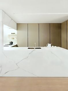 Very modern clean kitchen. White marble and doors for storage