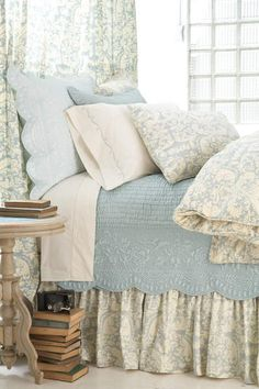 Nice soft blue, cream & white colour scheme for bedroom with lots of layering of quilts & blankets