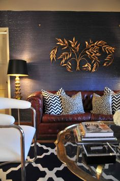 coffee table, blue grasscloth wallpaper, wall sculpture, chevron pillows, studded & tufted leather sofa