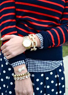 Shop this look on Lookastic:  http://lookastic.com/women/looks/crew-neck-sweater-bracelet-watch-dress-shirt-skater-skirt/8928  — Red and Navy Horizontal Striped Crew-neck Sweater  — Gold Bracelet  — Gold Watch  — Navy and White Gingham Dress Shirt  — Navy and White Polka Dot Skater Skirt