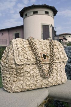 Ermanno's large brown bag featuring a weaved panel design and  chunky golden chain handles. All available at Splash By The Bea