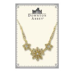 """Radiant and refined, this gilded statement necklace will transport you to the opulence and luxury of the Belle Époque era. A tantalizing trio of gold-toned stars illuminates your neckline with a sparkling selection of glittering crystals. This vintage inspired creation hangs from a delicate gold-tone chain. Adjustable from 16"""" to 19"""" length. Comes in a Downton Abbey gift box. (Box color may vary.)"""