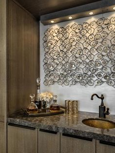"""Because it's often an entertaining focal point, the style of the wet bar is particularly important. Says designer Robin Baron of this glamorous example:""""Even awetbarneeds accessorizing. Textured walls along a sculptural and lit art installation create a great backdrop. Throw in a few key accessories that feel like they organically belong there, like decorative glasses anddecanters, and you set the stage for fabulous entertaining."""""""