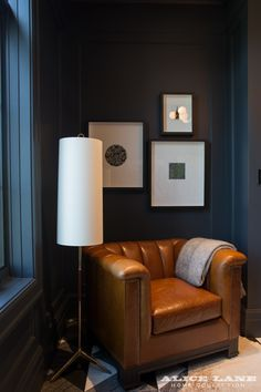 Masculine comfort. This little nook in a husband's office speaks to old world masculine design with the traditional leather tufted chair and bug art. But the space remains fresh and modern with a mid-century lamp style and our designer's dark gray custom paint mix for the walls and base/case.   French Moderne Manor Designed by Alice Lane   Featured in @Utahstyle See more of stunning French Moderne Manor:  https://alicelanehome.com/portfolio/french-moderne-manor/
