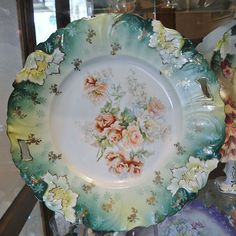 This is an unmarked rare size at 11 1/4 RS Prussia cake plate in the RS Steeple mold 3. Decorated with a cluster of small multicolored roses.