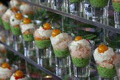 Layered shrimp cocktail in glass vessels on food station