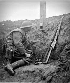 WWI, 7 Feb 1918; A sentry uses a box periscope in a trench on the 36th Division front, near Essigny. © IWM (Q 10688)