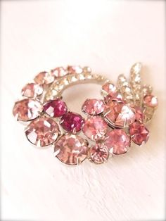 .  pink  piece of    Eisenberg jewelry from the 1940s. in particular is in excellent condition and still sparkles brightly. Its main attraction is the jeweled flower center piece. It has the Eisenberg signature.