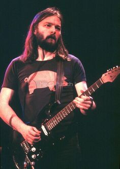 David Gilmour of Pink Floyd wearing what is likely an Animals tour t-shirt. The Black Strat has a rosewood fretboard neck (not original to the guitar). Before the band recorded The Wall, he would replace it with the maple neck it has now.