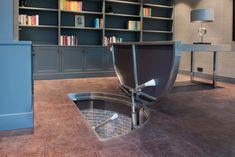 Dit vloerluik in Hilversum is vooral bijzonder door de speciale vorm. Omdat deze geplaatst is boven eenspiltrap heeft het vloerluik de vorm van een halve cirkel.  Er zijn geen wanden nodig zodat er optimaal gebruik gemaakt worden van de ruimte in dit kantoor.  Bij een verborgen vloerluik is de het frame gemaakt van RVS en de bekleding van hetzelfde materiaal als de vloer. Tegelwerk in dit geval.