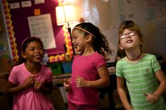 """Alicia Green, Lily Garcia and Ariana Cervantes, first grade students at Evans International Elementary School in District 49, dance and laugh during a 'brain break' between reading blocks Sept. 16. The Sand Creek Zone elementary school began a new curriculum and a school-wide schedule approach is started at the beginning of the 2015-2016 school year. """"It's a double dose of everything and it's already making a difference,"""" said their teacher, Julia Swonger, about the two reading blocks each…"""