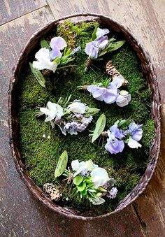 Whimsical forest wedding boutonnieres displayed on a bed of moss.   by Gavita Flora