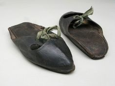 1780-1800, Black leather with pointed toe cap and separate bars, tying across instep with green ribbon. Slightly wedged sole. Manchester Galleries 1949.131